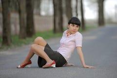 красивейшее усаживание дороги девушки Стоковая Фотография
