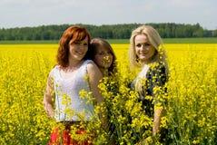 Красивейшие девушки на поле rapeseed Стоковые Изображения RF