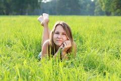 красивейшие детеныши женщины зеленого цвета травы лежа Стоковые Фото