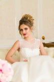 красивейшие детеныши портрета невесты Девушка представляет в гостиничном номере Дама сидит с букетом роз  Стоковая Фотография RF