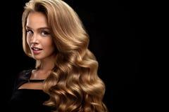 красивейшие курчавые волосы Женская модель красоты с волосами тома стоковое изображение