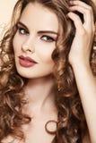 Красивейшие модельные касатьются ее длинним глянцеватым курчавым волосам Стоковое фото RF