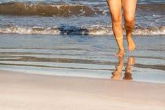 Красивейшие ноги женщины на пляже на заходе солнца Стоковая Фотография RF
