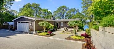 Красивейший дом с гаражом, взглядом озера и большим двором перед входом. Стоковые Изображения RF