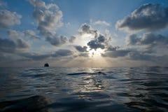 Красивейший заход солнца с пасмурным голубым небом над водой моря Стоковое фото RF