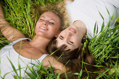 красивейший зеленый цвет травы кладет 2 женщин молодых Стоковые Фотографии RF