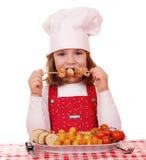 Кашевар маленькой девочки ест зажженное мясо цыпленка Стоковые Изображения