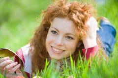 красивейший красный цвет зеленого цвета травы девушки с волосами излишек Стоковая Фотография