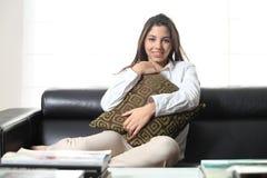 Красивейший подросток на кресле на дому обнимая валик Стоковая Фотография RF