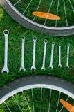 красивейший ремонт горы bike ремонтируя ся женщину Инструменты для ремонтировать велосипед на траве между колесами Стоковое Изображение