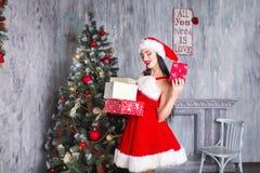 красивейший claus одевает носить santa девушки сексуальный Усмехаясь женщина с большим и малым подарком Женщины на платье и шляпе Стоковая Фотография RF