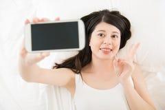 Красивое азиатское selfie взятия женщины с smartphone на кровати Стоковая Фотография
