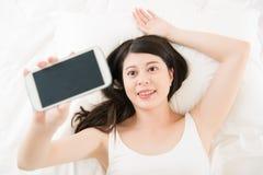 Красивое азиатское selfie взятия женщины с smartphone на кровати Стоковые Изображения