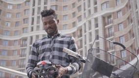 Красивое Афро-американское положение человека с велосипедом перед высоким строя шлемом велосипеда удерживания небоскреба в руках акции видеоматериалы