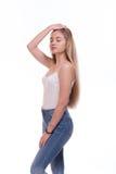 Красивое белокурое положение молодой женщины На белой предпосылке Стоковые Фотографии RF