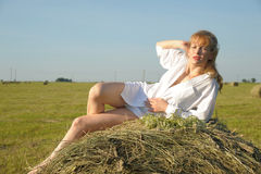 Красивое белокурое sittitng девушки страны на желтом сене с пуком цветков Стоковая Фотография