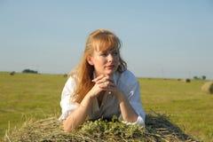 Красивое белокурое sittitng девушки страны на желтом сене с пуком цветков Стоковые Изображения RF