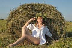 Красивое белокурое sittitng девушки страны на желтом сене с пуком цветков Стоковые Изображения