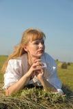 Красивое белокурое sittitng девушки страны на желтом сене с пуком цветков Стоковая Фотография RF