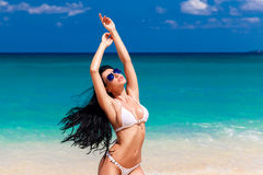 Красивое брюнет в белом бикини на тропическом пляже Стоковое фото RF