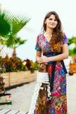 Красивое брюнет в красочном длинном платье стоя на пляже около бара на предпосылке пальм Стоковое фото RF