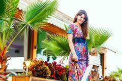 Красивое брюнет в красочном длинном платье стоя на пляже около бара на предпосылке пальм Стоковые Фото