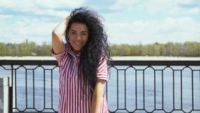 Красивое брюнет в платье striped пинком посылает поцелуй воздуха к камере сток-видео