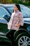 Красивое брюнет в светлой меховой шыбе и черных брюках стоит около автомобиля на день осени солнечный стоковое изображение