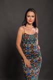 Красивое брюнет в стильном дизайнерском платье на темной предпосылке стоковое изображение