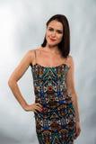 Красивое брюнет в стильном дизайнерском платье на темной предпосылке стоковое фото rf