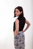 Красивое брюнет в стильном дизайнерском платье на темной предпосылке стоковые фотографии rf
