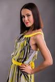 Красивое брюнет в стильном дизайнерском платье на темной предпосылке стоковые фото