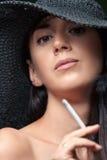 Красивое брюнет в шляпе курит Стоковые Фотографии RF