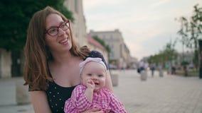 Красивое брюнет держа младенца на ее коленях акции видеоматериалы
