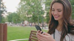 Красивое брюнет используя мобильный телефон Outdoors сток-видео