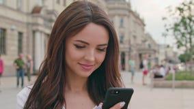 Красивое брюнет используя мобильный телефон Outdoors акции видеоматериалы