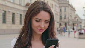 Красивое брюнет используя мобильный телефон Outdoors видеоматериал