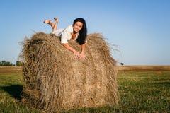 Красивое брюнет лежит на стоге сена стоковое фото
