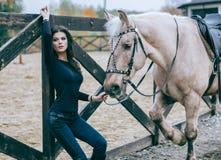 Красивое брюнет представляя с лошадью в после полудня осени на ранчо страны Фото образа жизни способ простыни кладет детенышей бе Стоковая Фотография RF