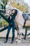 Красивое брюнет представляя с лошадью в после полудня осени Фото образа жизни способ простыни кладет детенышей белой женщины фото Стоковая Фотография RF