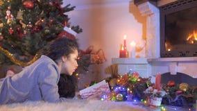 Красивое брюнет прочитало книгу около рождественской елки акции видеоматериалы