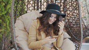 Красивое брюнет сидит на улице в шкентеле, пошатывает, читает текстовое сообщение от ее человека, усмехается, носится черноту акции видеоматериалы