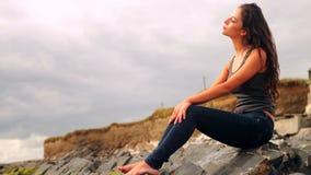 Красивое брюнет сидя на утесах пляжем акции видеоматериалы