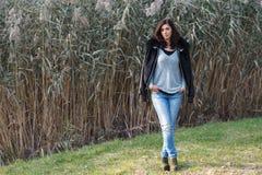 Красивое брюнет стоя на предпосылке тростников Стоковое Фото
