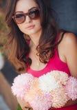 Красивое брюнет с букетом розовых цветков стоковое изображение