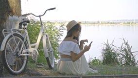 Красивое брюнет читает книгу на smartphone сидя на речном береге около ее велосипеда города сток-видео
