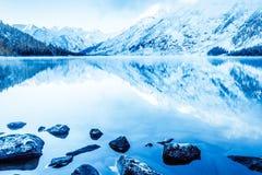 Красивое голубое озеро в горах Плоская поверхность зеркала воды под облаками стоковое фото rf