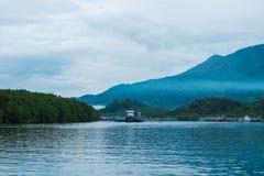 Красивое голубое море, деревня рыболова на побережье и имеют большое moun Стоковые Изображения