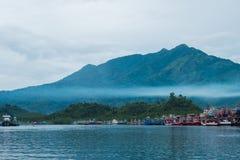 Красивое голубое море, деревня рыболова на побережье и имеют большое moun Стоковое Фото