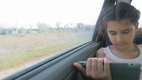 Красивое движение маленькой девочки использует таблетку с открытой цифровой картой в ем, говорить и усмехаться усаживание девушки видеоматериал